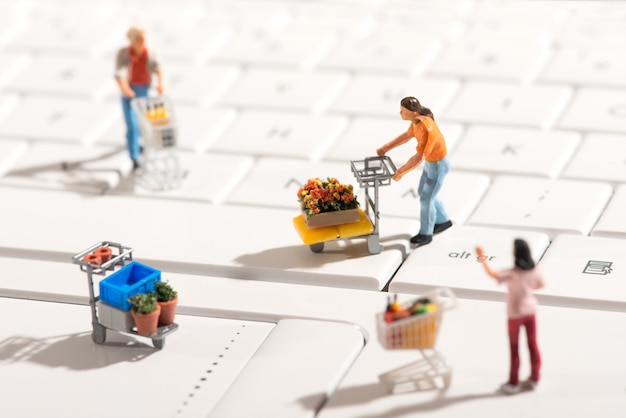 Miniature people shopping for items with carts