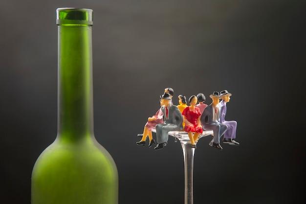 미니어처 사람들은 병 근처의 와인 잔 가장자리에 앉아 있습니다.