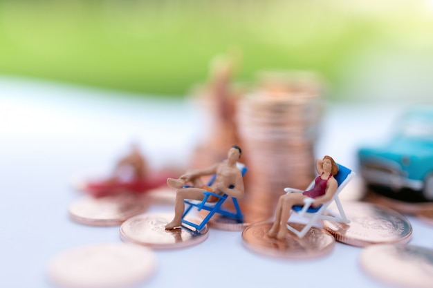 Miniature people sitting the beach with coins