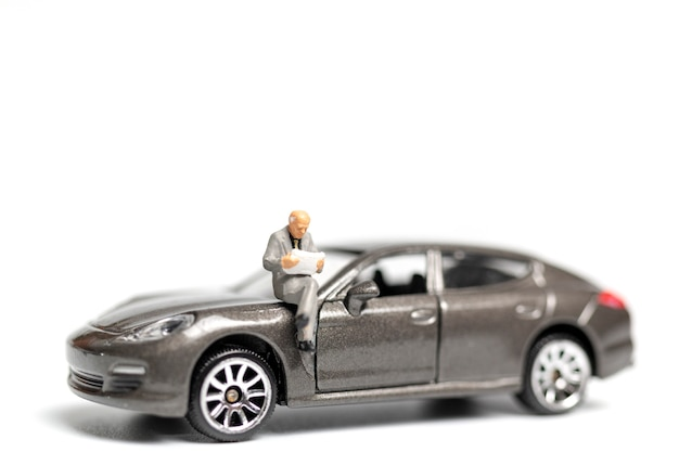 Miniature people sitting on car with copy space