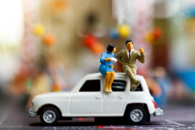 Miniature people sitting on the car