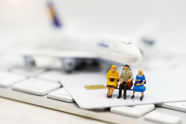 Miniature people sitting on credit card with keyboard and airplane.