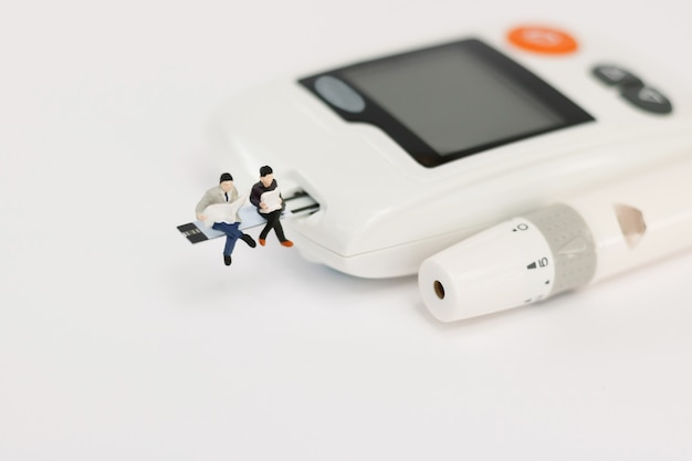 Miniature people sitting on a glucose meter of diabetes ,  health care concept.
