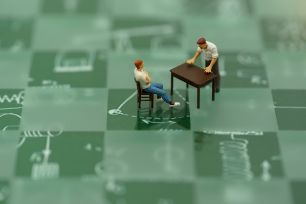 Miniature people sitting green checkerboard.