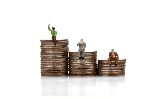 Миниатюрные люди, сидящие на стопке монет, изолируют