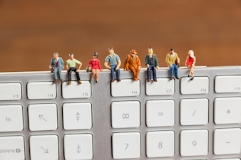 Miniature people sitting on top of keyboard