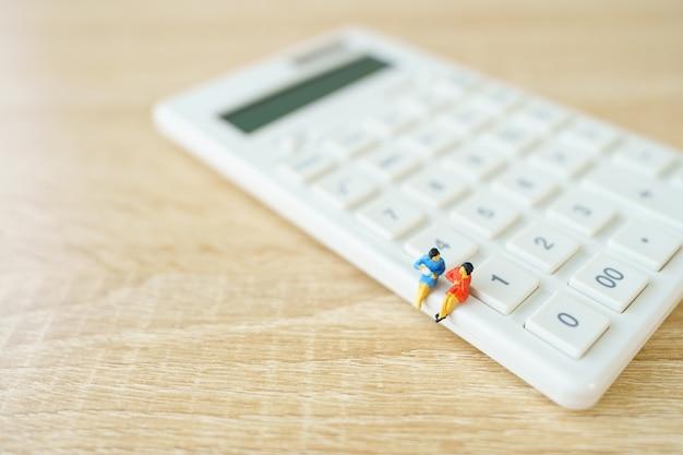 Миниатюрные люди, сидящие на белом калькуляторе, используя в качестве фона бизнес-концепцию