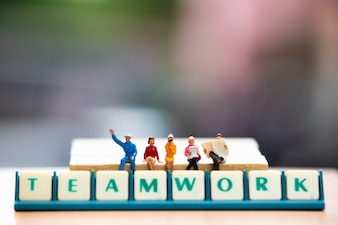 Miniature people sitting on wooden block and teamwork words
