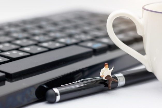 Miniature people sitting on pen with keyboard and cup of coffee.