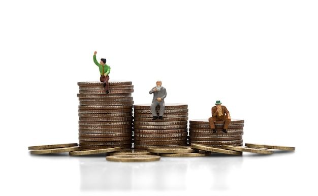 Miniature people sitting on a stack of coins isolate