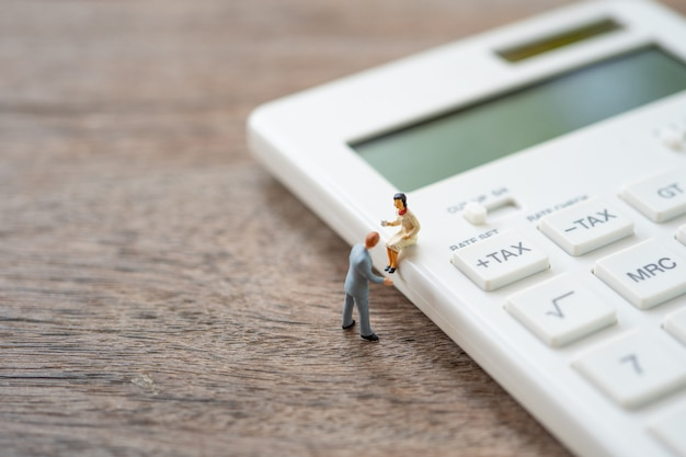 Miniature people sitting on white calculato