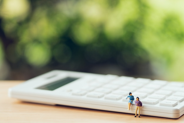 Miniature people sitting on white calculator using as background business concept