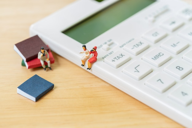 Miniature people sitting on white calculator using as background business