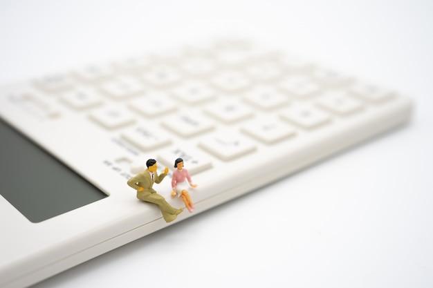 Miniature people sitting on white calculator