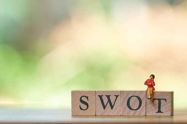 Miniature people sitting on wood word swot