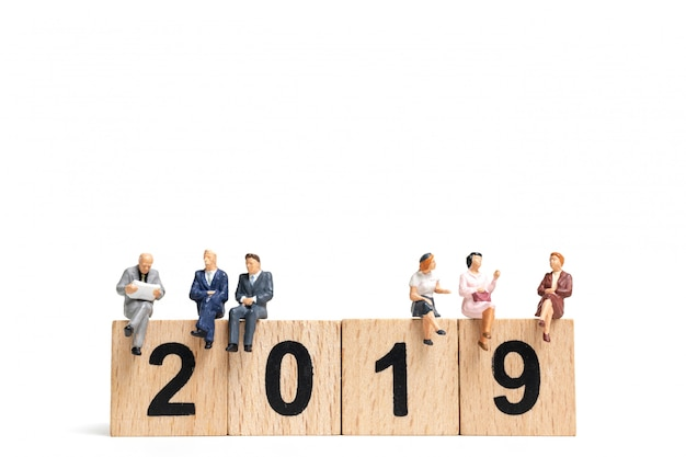 Miniature people sitting on wooden block number 2019