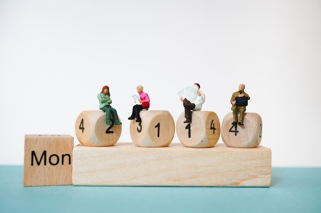 Miniature people sitting on wooden block number