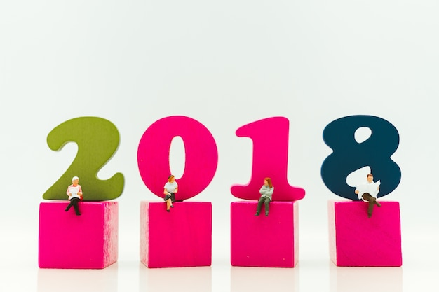 Miniature people sitting on year 2018 wooden block using as social and business concept - vintage fi
