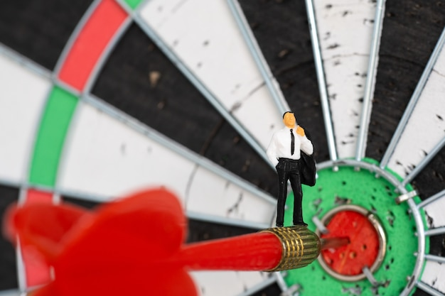 ミニチュアの人々:ダーツボードのターゲットセンターを打つ赤いダーツの矢の中小企業の男。