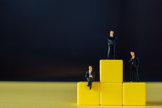 미니어처 사람들 : 검은 색 표면의 노란색 연단에 서있는 중소 기업인 인물