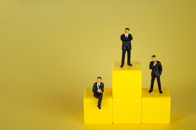 미니어처 사람들 : 노란색 표면이있는 노란색 연단에 서있는 중소 기업인 인물
