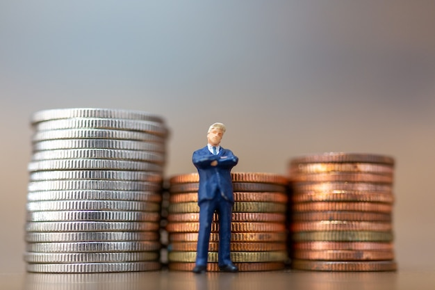 Miniature people: small businessmen standing with stack of coins , business growth concept.