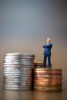 Миниатюрные люди: мелкие предприниматели, стоящие со стопкой монет, концепция роста бизнеса.