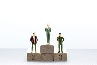 Miniature people small figures businessmen stand on wooden podium