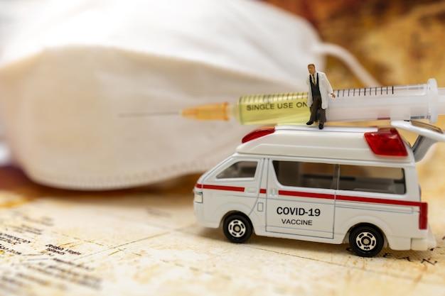 미니어처 사람들은 의료용 마스크와 covid-19 백신 주사기를 들고 구급차에 서 있습니다. 백신 및 의료 의료 개념.