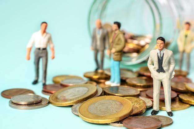 미니어처 사람들이 동전 사업과 팀 개념에 서
