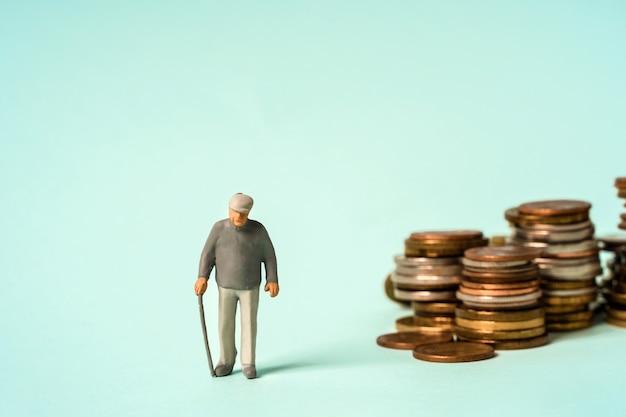 미니어처 사람들은 동전에 서서 노인과 저축 연금