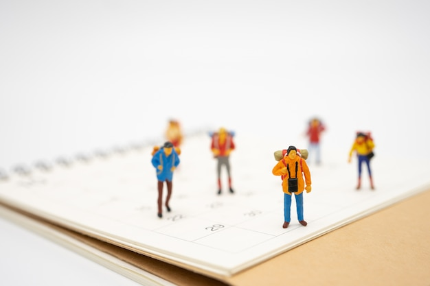 Miniature people stand on the walkway the beginning of the journey to reach the goal.