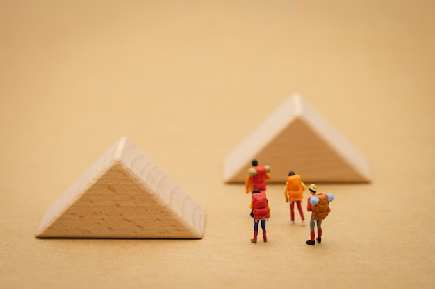 Miniature people stand on the walkway is a block means the beginning of the journey