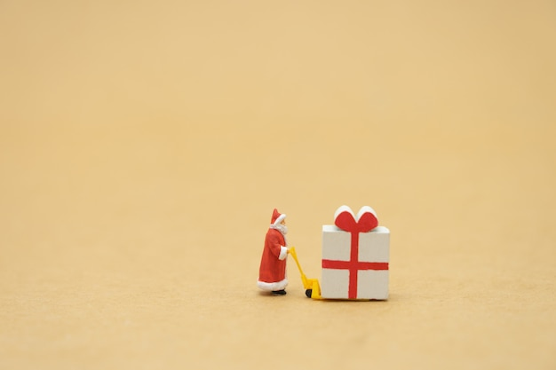 Miniature people standing on christmas tree celebrate christmas on december 25