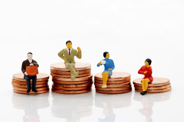Miniature people standing on coins
