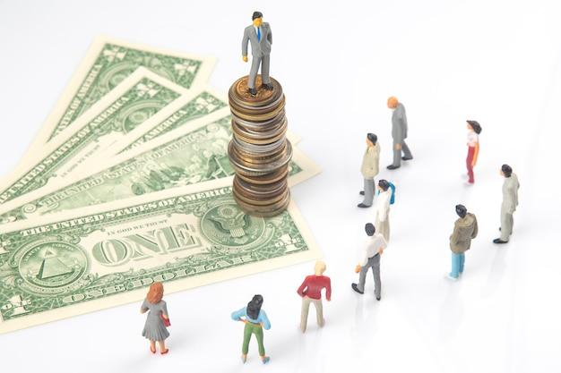 달러 지폐 근처에 서있는 미니어처 사람들과 동전 더미에 서있는 사람