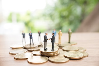 Miniature people standing on coin