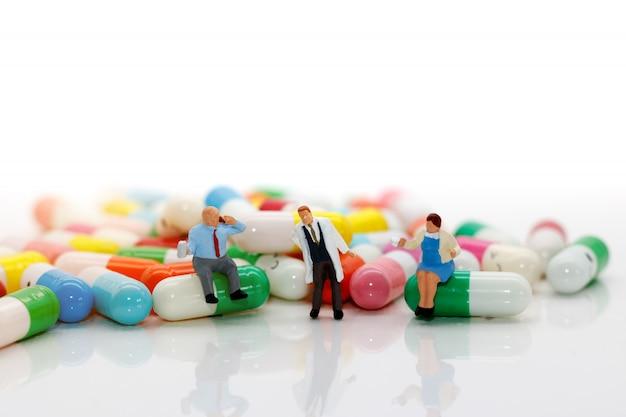 Miniature people standing on pills