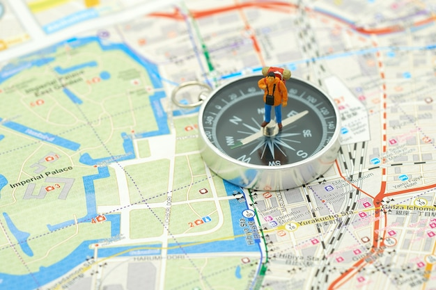 Miniature people standing travel planner on a compass with japan map