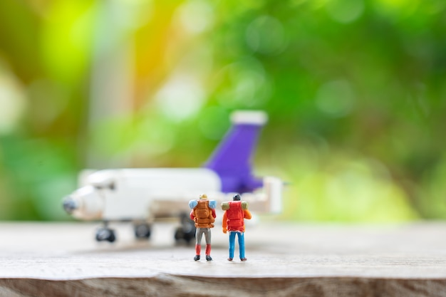 Miniature people standing travel planner with plane model