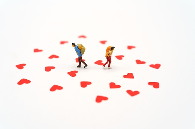 Miniature people standing with heart shaped red paper. red heart is the promise of love.