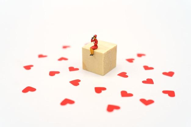 하트 모양의 빨간 종이로 서 미니어처 사람들. 붉은 마음은 사랑의 약속입니다.