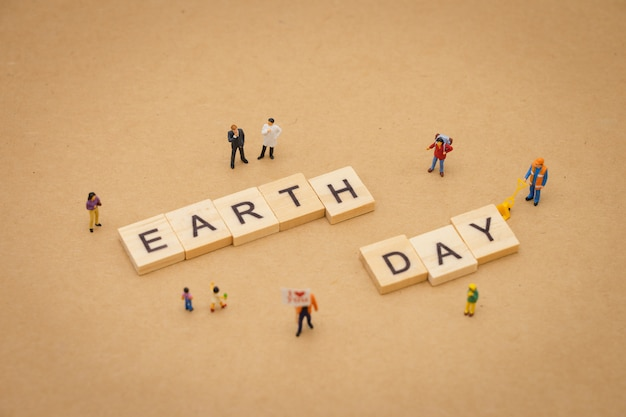 Miniature people standing with wood word earth day using as background universal day concept