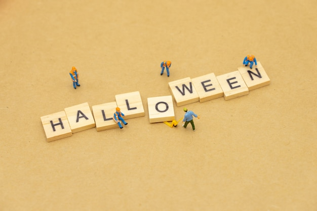 Miniature people standing with wood word halloween using as background universal day