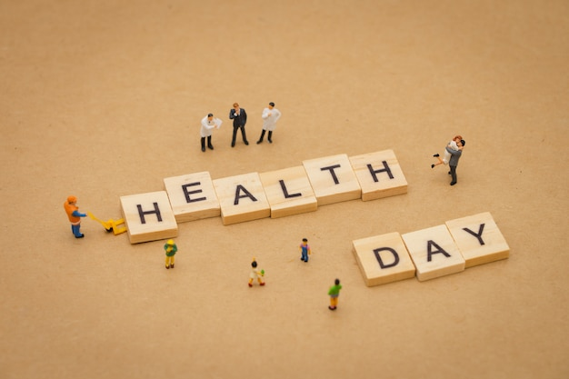 Miniature people standing with wood word health day using as background universal day