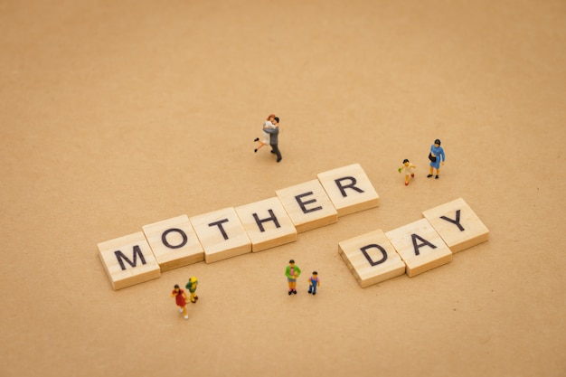 Miniature people standing with wood word mother day using as background universal day