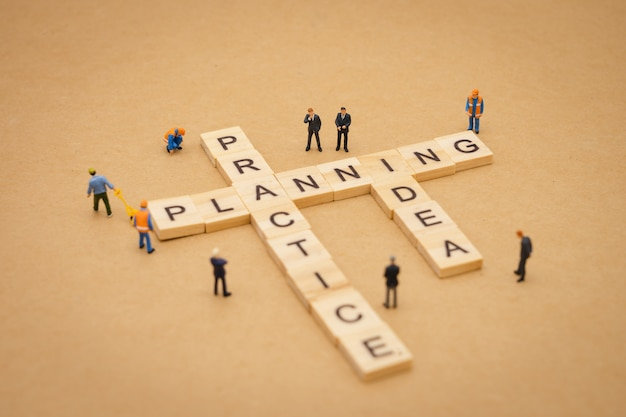 Miniature people standing with wood word planning , practice and idea