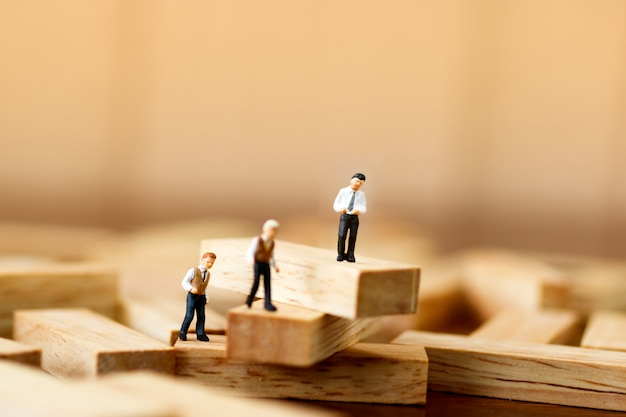 Miniature people standing on wooden blocks