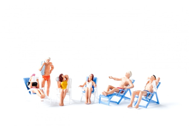 Miniature people sunbathing on deck chairs, summer time concept