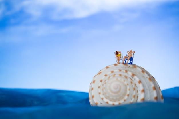 Miniature people sunbathing on a seashell with blue sky